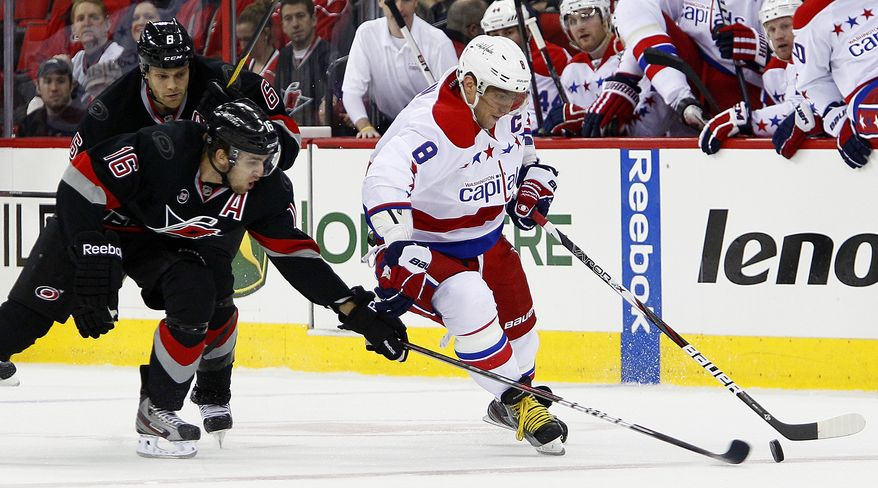 Alex Ovechkin (8) of the Washington Capitals has the puck poked away by the Carolina Hurricanes' Brandon Sutter (16), with the Hurricanes' Tim Gleason nearby, during the first period of an NHL hockey game in Raleigh, N.C., on Monday, Feb. 20, 2012. (AP Photo/Karl B. DeBlaker)