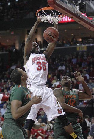 Maryland forward James Padgett dunks on Miami's Kenny Kadji, left, and Reggie Johnson in College Park, Md., Tuesday, Feb. 21, 2012. (AP Photo/Patrick Semansky)