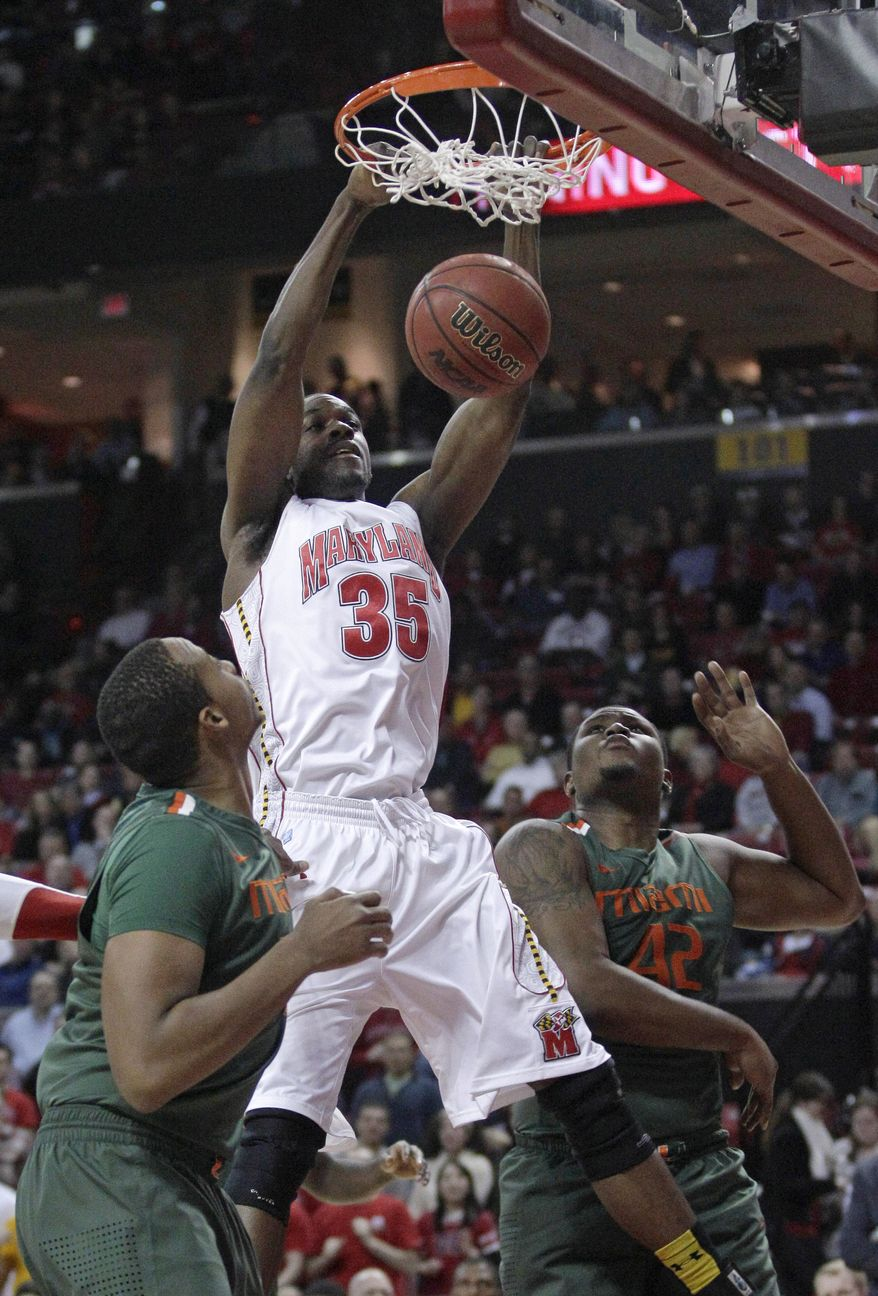 Maryland forward James Padgett dunks on Miami's Kenny Kadji, left, and Reggie Johnson in College Park, Md., Tuesday, Feb. 21, 2012. (AP Photo/Patrick Semansky)