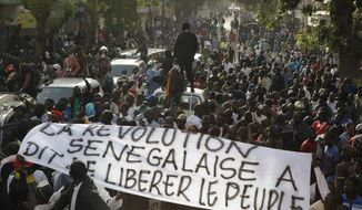 "Anti-government protesters carry a banner reading ""The Senegalese revolution said to liberate the people,"" as they are blocked by police from reaching Independence Square in central Dakar, Senegal, on Feb. 21, 2012. (Associated Press)"