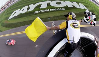 Tony Stewart, last year's Sprint Cup champion, takes the checkered flag in the first of two 150-mile qualifying races for the Daytona 500. NASCAR's biggest race is Sunday. (Associated Press)