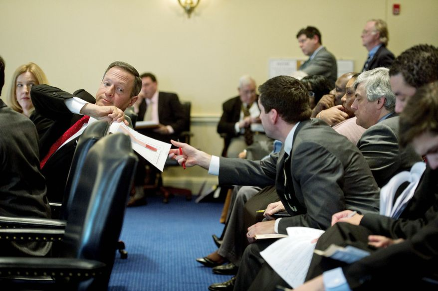 ** FILE ** Maryland Gov. Martin O'Malley passes paperwork to a staff member during a House Economic Matters Committee hearing on Feb. 23, 2012, in Annapolis. Mr. O'Malley testified on his offshore wind energy bill, a proposal he says would lower reliance on fossil fuels. (Rod Lamkey Jr./The Washington Times)