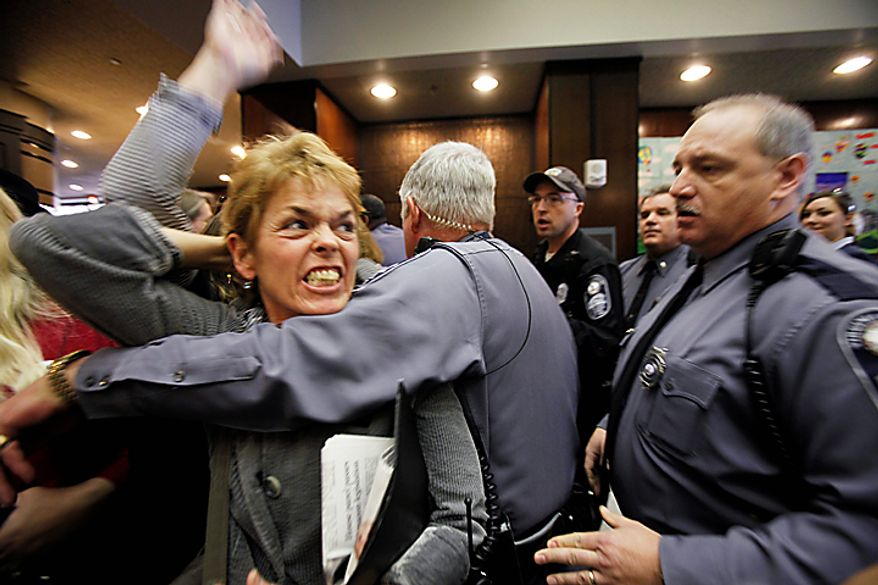 Pro-choice advocate Margaret Doyle of Richmond is removed by Capitol Police from the General Assembly Building in Richmond after a bill that states human life begins at conception passed the Senate Education and Health committee on Thursday, Feb. 23, 2012. (AP Photo/Richmond Times-Dispatch, Bob Brown)