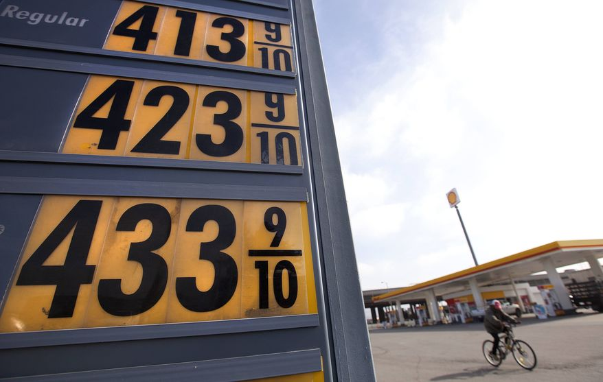 **FILE** Gasoline prices are displayed Feb. 21, 2012, as a man rides his bicycle past them at a station in Oakland, Calif. (Associated Press)