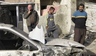 ** FILE ** People inspect the scene of a car bomb explosion Feb. 23, 2012, in Karradah in downtown Baghdad. Iraqi officials said a string of attacks across Baghdad killed and injured dozens of people. (Associated Press)