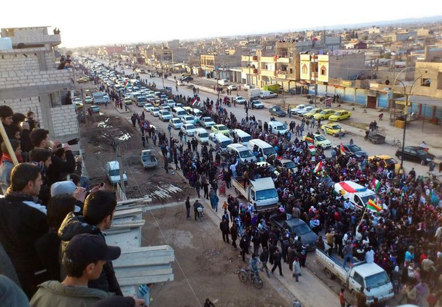 Anti-Syrian-regime protesters hold up Kurdish flags during a rally in the northeastern town of Qamishli, Syria, on Wednesday, Feb. 22, 2012, in this image taken by a citizen journalist. (AP Photo/Local Coordination Committees in Syria)