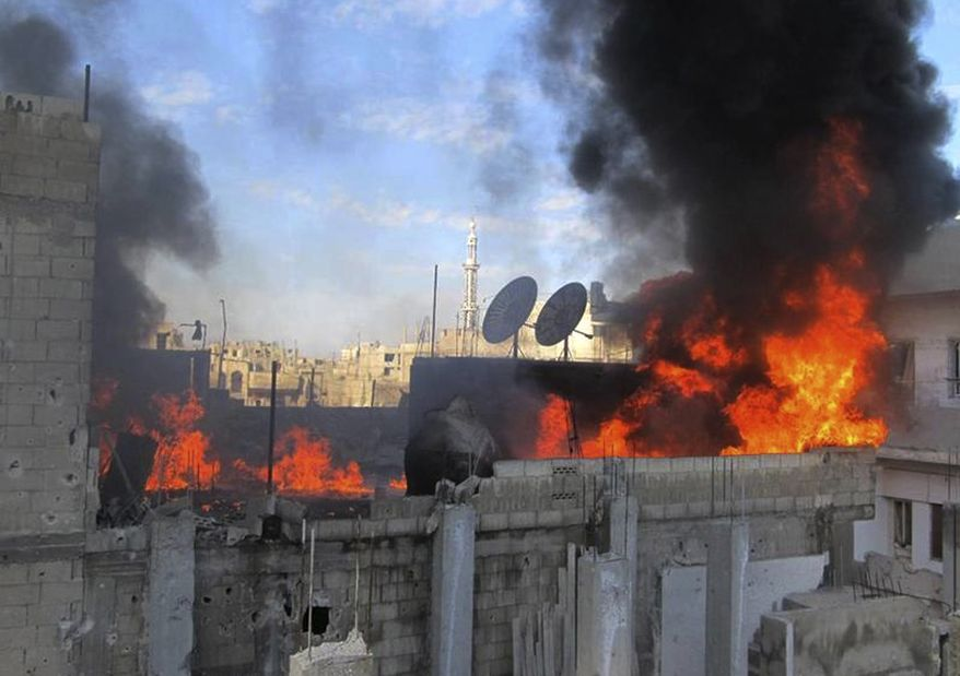 Flames rise from a house in the Baba Amr neighborhood in Homs, Syria, on Wednesday, Feb. 22, 2012, after shelling by government troops. This photo was taken by a citizen journalist and supplied by the Local Coordination Committees activist group. (AP Photo/Local Coordination Committees in Syria)