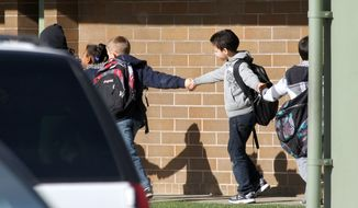 Students hold hands as they are led along a walkway at Armin Jahr Elementary School in Bremerton, Wash., following the shooting of an 8-year-old female student there on Wednesday, Feb. 22, 2012. (AP Photo/Kitsap Sun, Larry Steagall)