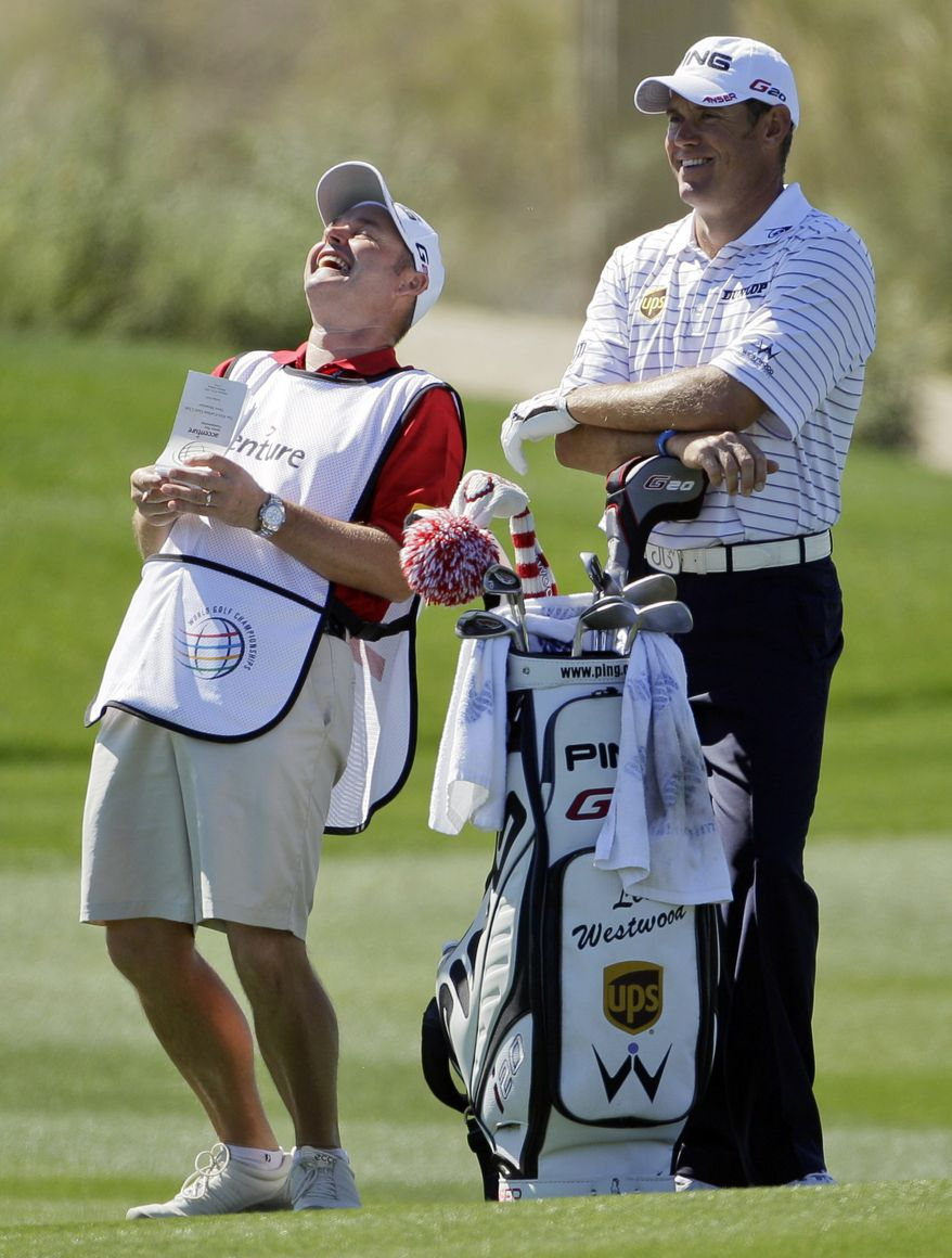 Lee Westwood, right, laughs with his caddie while waiting to take his shot on the seventh fairway against Nick Watney during the Match Play Championship golf tournament on Friday, Feb. 24, 2012, in Marana, Ariz. (AP Photo/Eric Risberg)