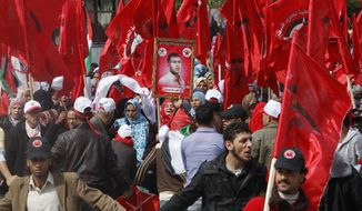 Palestinian supporters of the Democratic Front for the Liberation of Palestine wave their party's red flags during a Feb. 23, 2012, rally in Gaza City celebrating 43 years since its founding. (Associated Press)