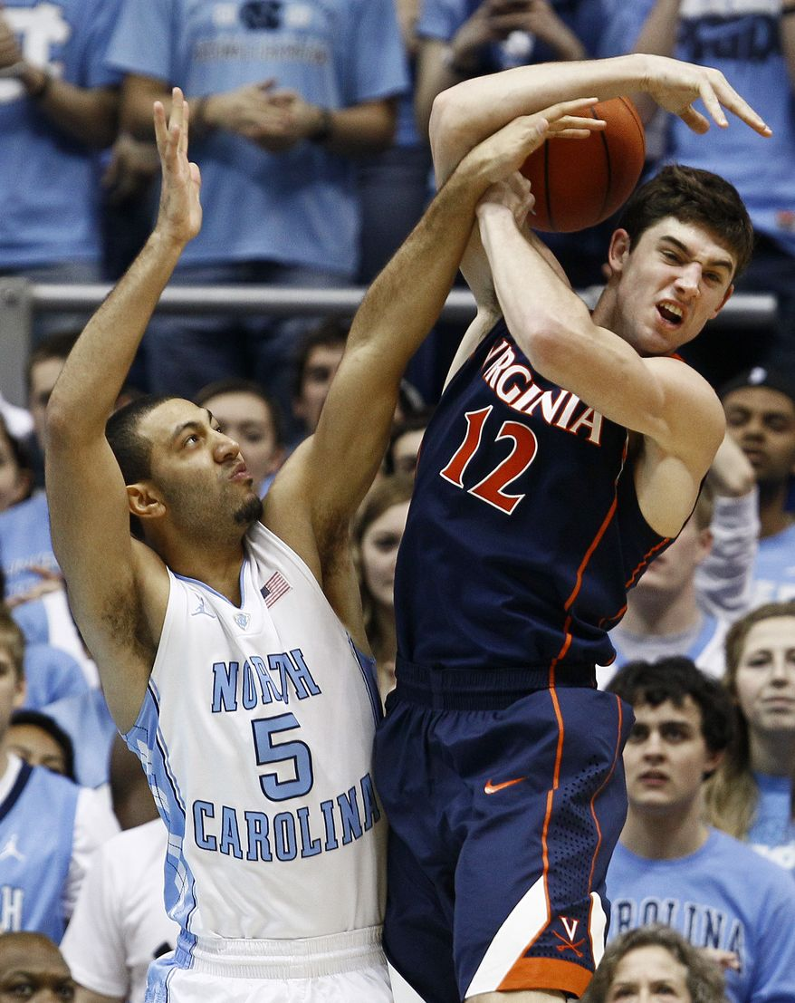 North Carolina's Kendall Marshall and Virginia's Joe Harris struggle for a rebound during the first half in Chapel Hill, N.C., Saturday, Feb. 11, 2012. Virginia lost 70-52. (AP Photo/Gerry Broome)