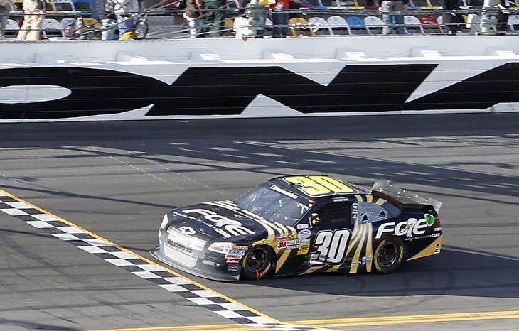 James Buescher crosses the finish line to win the Nationwide Series NASCAR Drive4COPD 300 auto race at Daytona International Speedway in Daytona Beach, Fla., Saturday, Feb. 25, 2012. (AP Photo/Terry Renna)