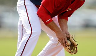 Washington Nationals third baseman Ryan Zimmerman fields a ground ball during the team's first official spring training full squad workout Saturday, Feb. 25, 2012, in Viera, Fla. (AP Photo/Julio Cortez)
