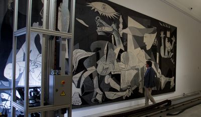 "Jorge Garcia Gomez-Tejedor, head of conservation at Reina Sofia Museum in Madrid, examines Pablo Picasso's ""Guernica"" as a camera mounted on a mobile robotlike structure moves across the painting to inspect it for damage. (Associated Press)"