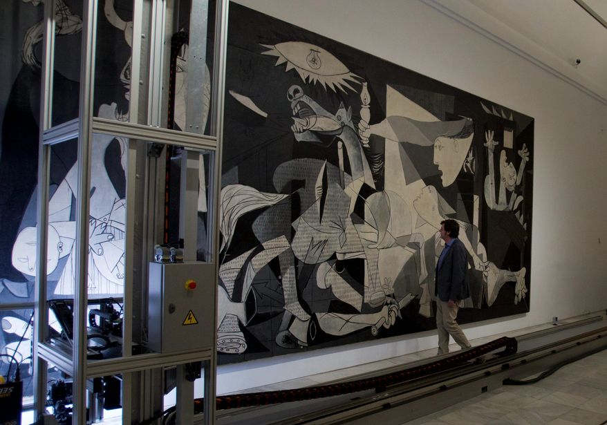 """Jorge Garcia Gomez-Tejedor, head of conservation at Reina Sofia Museum in Madrid, examines Pablo Picasso's """"Guernica"""" as a camera mounted on a mobile robotlike structure moves across the painting to inspect it for damage. (Associated Press)"""