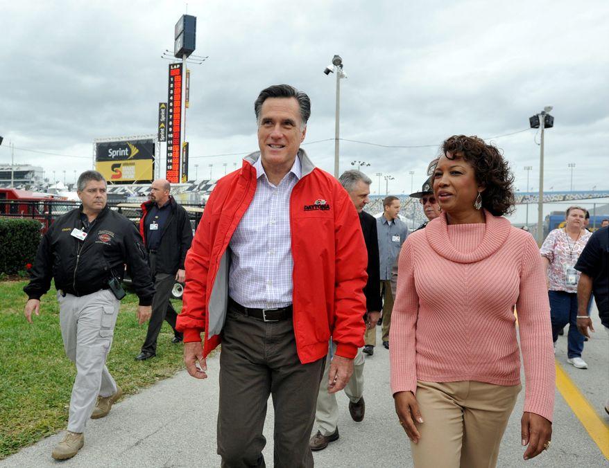 Republican presidential candidate and former Massachusetts Gov. Mitt Romney (left) walks Feb. 26, 2012, with Florida Lt. Gov. Jennifer Carroll before the NASCAR Daytona 500 Sprint Cup series auto race at Daytona International Speedway in Daytona Beach, Fla.. (Associated Press)