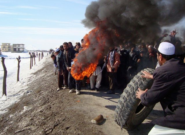 Afghans burn tires in Muhammad Agha in Logar province, which is south of Kabul, on Saturday during an anti-U.S. demonstration over burning of Korans at a U.S. military base. Despite a week of attacks and violent protests, there are no plans to accelerate withdrawal from the country. (Associated Press)