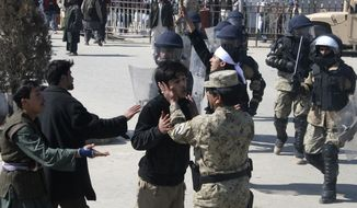An Afghan policeman calms down a protester in Kunduz, Afghanistan, on Saturday, Feb. 25, 2012, during an anti-U.S. demonstration prompted by the burning of Korans and other religious materials by U.S. forces at the Bagram Airfield earlier in the week. (AP Photo/Ezatullah Pamir)