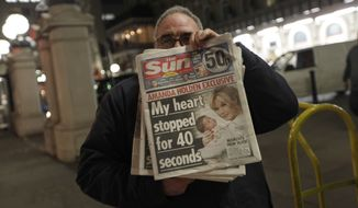 A newsdealer poses with the first edition of the Sunday Sun weekly tabloid in central London late on Saturday, Feb. 25, 2012. The paper is media mogul Rupert Murdoch's newest publication. (AP Photo/Lefteris Pitarakis)