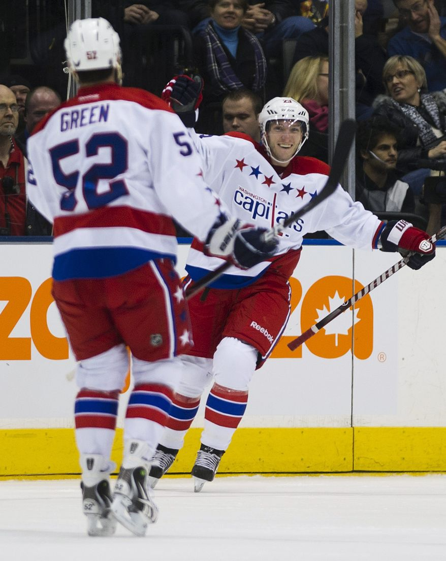 Washington Capitals' Keith Aucoin, right, celebrates his first goal of the season with teammate Mike Green while playing against the Toronto Maple Leafs during second-period NHL game action in Toronto, Saturday, Feb. 25, 2012. (AP Photo/The Canadian Press, Nathan Denette)