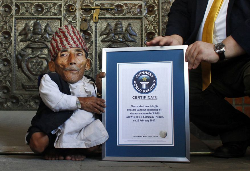 Nepal's Chandra Bahadur Dangi receives a certificate from Craig Glanday, editor-in-chief of Guinness World Records, after being declared the world's shortest living man and shortest man ever by the Guinness Book of Records at a ceremony in Katmandu, Nepal, on Sunday, Feb. 26, 2012. (AP Photo/Niranjan Shrestha)