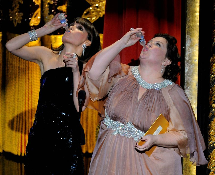 """Members of the cast of """"Bridesmaids"""" Rose Byrne and Melissa McCarthy drink a toast to Martin Scorsese as they present an award during the 84th Academy Awards on Sunday, Feb. 26, 2012, in the Hollywood section of Los Angeles. (AP Photo/Mark J. Terrill)"""