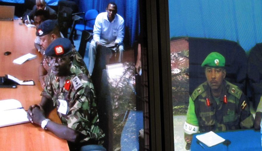 On adjoining screens, Maj. Gen. Fred Mugisha (right), the commander of African Union forces in Somalia, speaks on a video teleconference from Mogadishu with Col. Cyrus Oguna of the Kenyan military in Nairobi. (Associated Press)