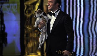 """Jean Dujardin holds Uggie after accepting the Oscar for best picture for """"The Artist"""" during the 84th Academy Awards on Sunday, Feb. 26, 2012, in the Hollywood section of Los Angeles. (AP Photo/Mark J. Terrill)"""
