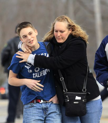 Doug Gasper, a ninth-grader at Chardon High School, is hugged Feb. 27, 2012, by his mother, Sandy, as they leave Maple Elementary School in Chardon, Ohio. Students assembled at Maple Elementary School after a gunman opened fire inside the high school's cafeteria at the start of the school day, wounding four students, officials said. (Associated Press)