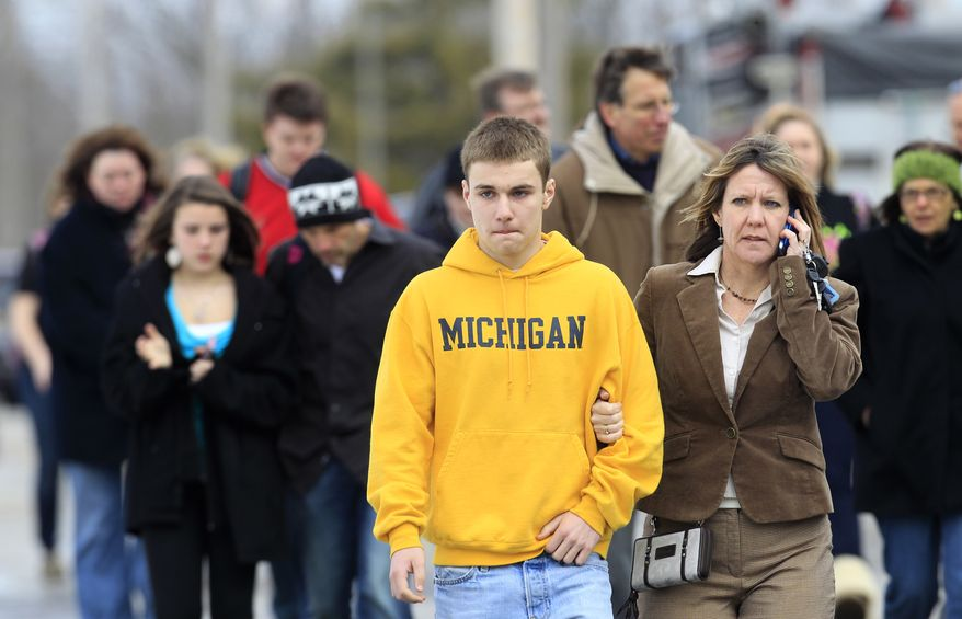 Students leave with their parents from Maple Elementary School after a shooting at Chardon High School on Monday, Feb. 27, 2012, in Chardon, Ohio. A suspect is in custody. (AP Photo/Tony Dejak)
