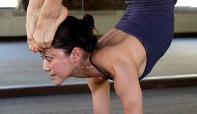 ASSOCIATED PRESS Yoga teacher Kyoko Katsura demonstrates the handstand scorpion pose. Some want to see competitive yoga posing in the Olympics.