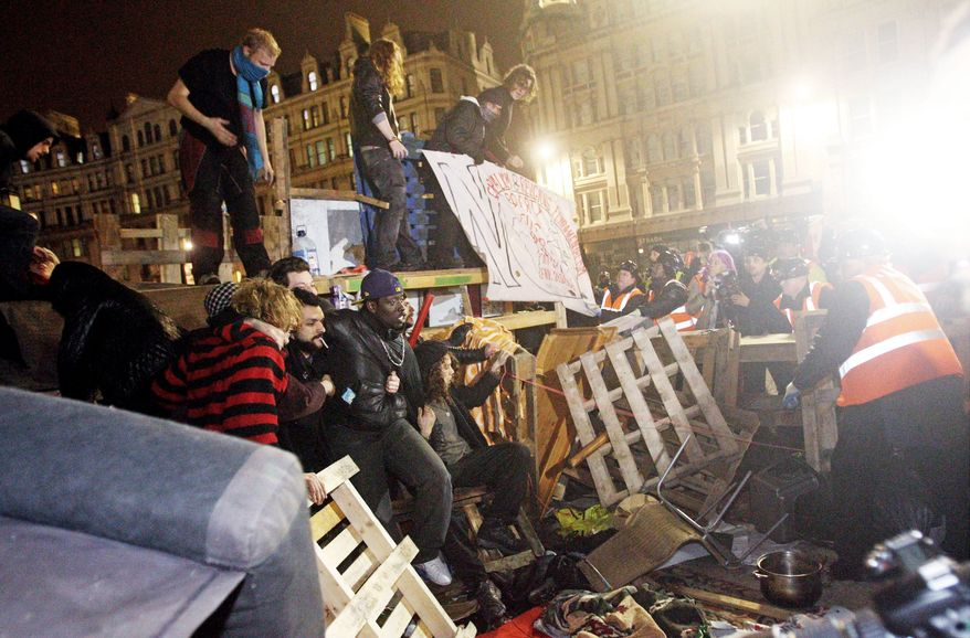 Demonstrators resist an effort by police to clear out the Occupy London camp outside St. Paul's Cathedral on Tuesday. The police removed tents from the anti-capitalist protest camp in London. The High Court ruled that the eviction of the Occupy London protest camp could proceed. (Associated Press)