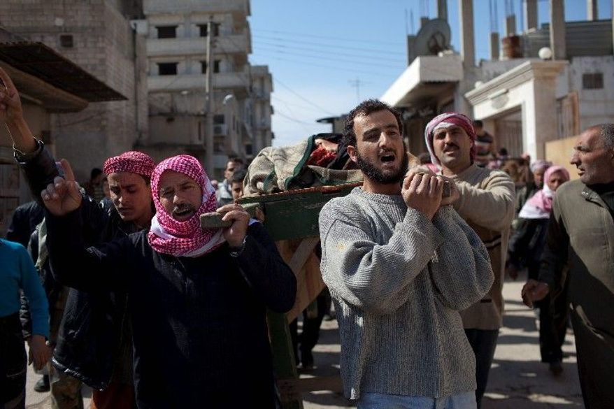 Syrian villagers in Sarmin on Tuesday carry the body of Ghassan Ali, who was killed during clashes between the Free Syrian Army and government forces. An uprising to oust authoritarian President Bashar Assad began nearly a year ago. (Associated Press)