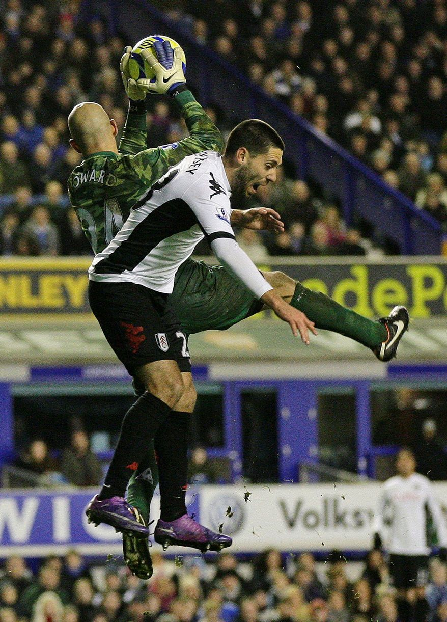 Everton's goalkeeper Tim Howard, left, vies for the ball against Fulham's Clint Dempsey during their FA Cup fourth round soccer match at Goodison Park, Liverpool, England, Friday Jan. 27, 2012. (AP Photo/Tim Hales)