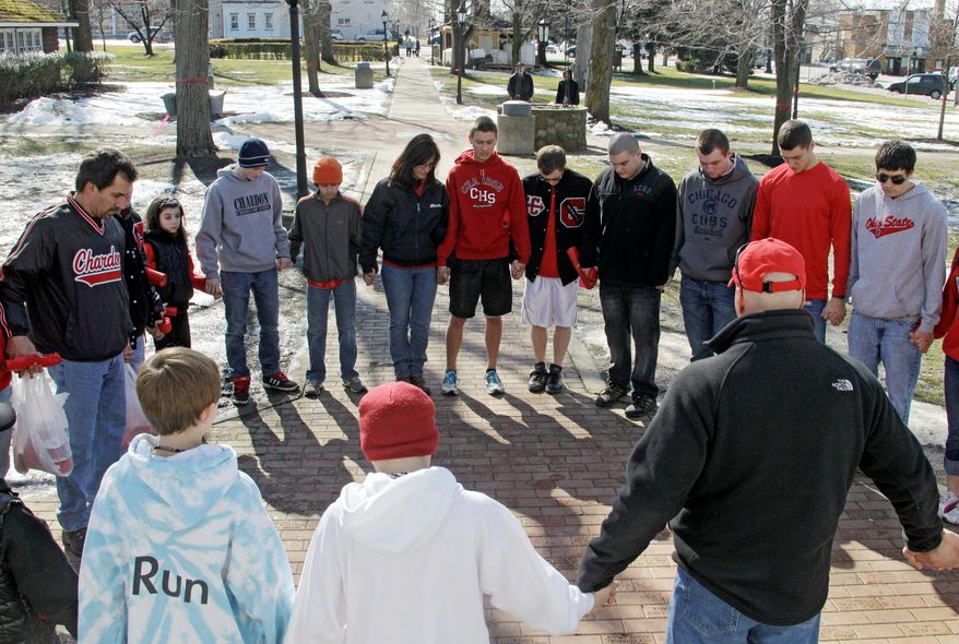Students and parents pray for victims of a school shooting on the square in Chardon, Ohio, on Tuesday. A gunman opened fire inside the Chardon High School cafeteria at the start of the school day on Monday. The community offered grief counseling to students, staff and others at area schools. (Associated Press)
