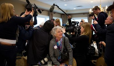 Helen Kilgere with the Dubuque Rotary Club gets squeezed by reporters and videographers trying to get close to former House Speaker Newt Gingrich following his campaign speech to the civic organization at the Dubuque Golf & Country Club in Dubuque, Iowa, on Tuesday, Dec. 27, 2011. (Andrew Harnik/The Washington Times)