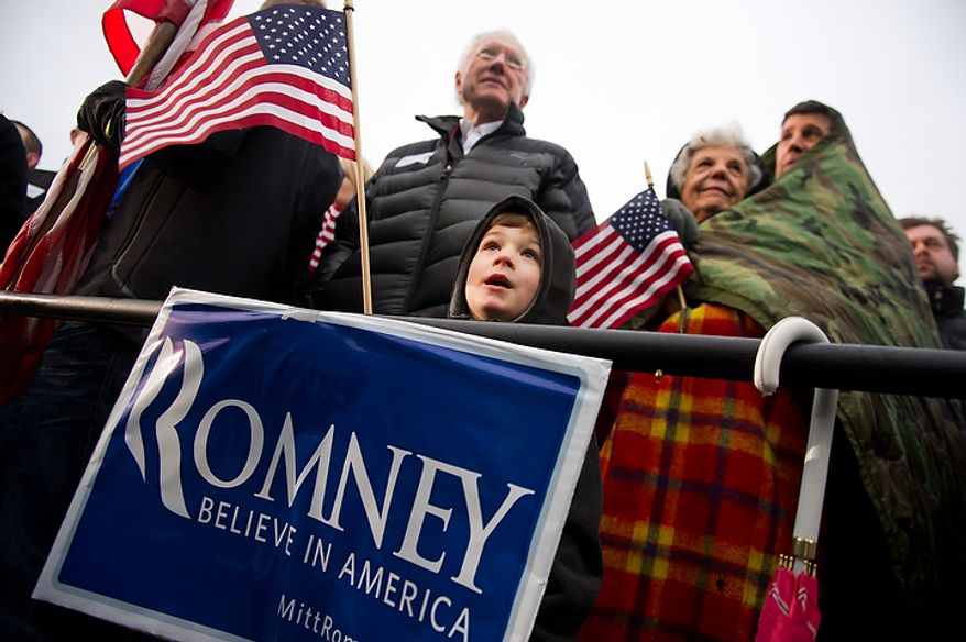 Bill Koenig (left) of West Des Moines, Iowa, with his 5-year-old grandson, Graham Kenworthy, braves the cold and rain alongside Marcella Yochum and her son, Scott Yochum, to see Republican presidential candidate Mitt Romney at an early-morning rally at a Hy-Vee grocery store in West Des Moines on Friday, Dec. 30, 2011. (Andrew Harnik/The Washington Times)