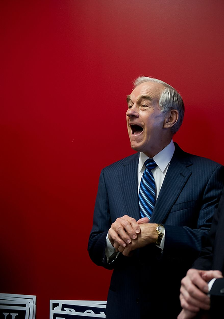Rep. Ron Paul, Texas Republican, laughs as he is complimented on being punctual upon his arrival to speak to supporters of his presidential campaign at a Jasper County town-hall meeting on the inner track of the Iowa Speedway in Newton, Iowa, on Wednesday, Dec. 28, 2011. (Andrew Harnik/The Washington Times)