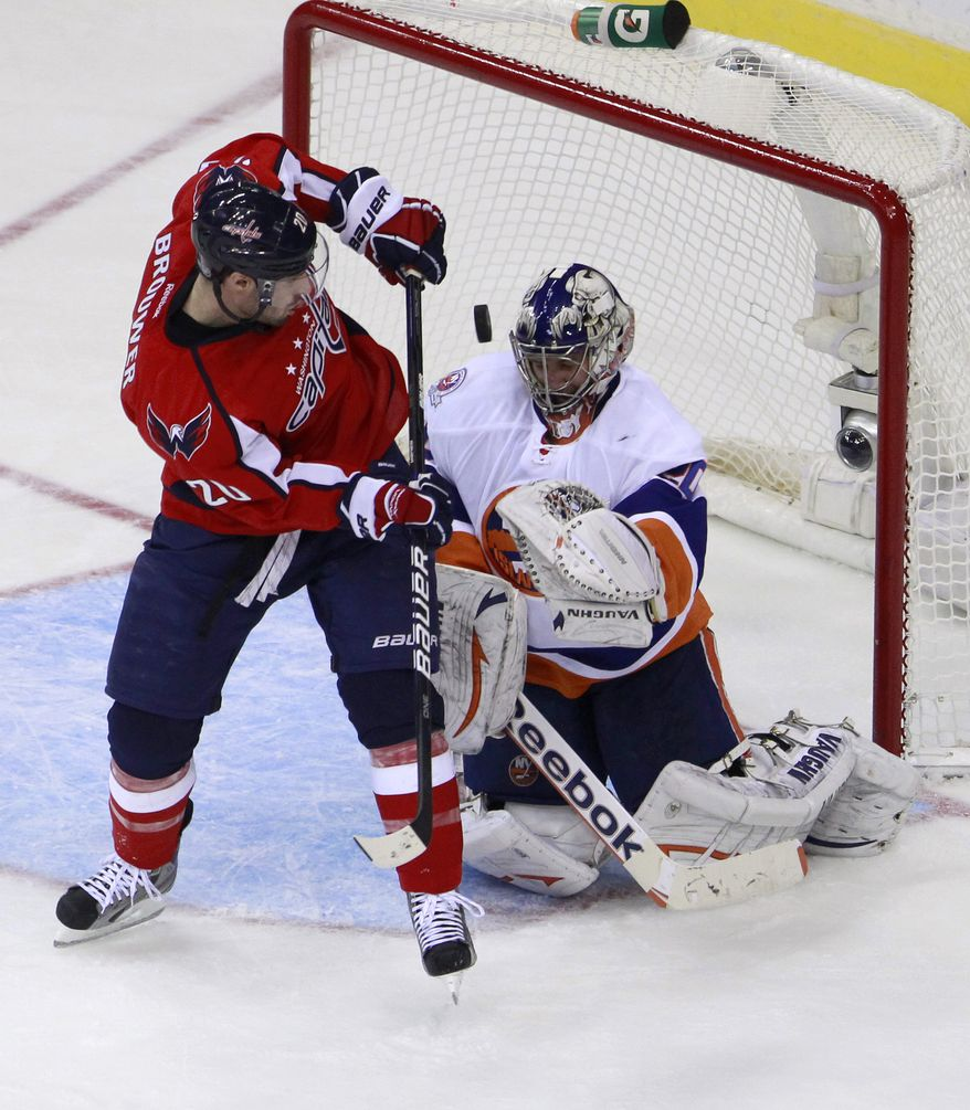 New York Islanders goalie Evgeni Nabokov deflects the puck in front of Washington Capitals left wing Troy Brouwer during the second period Tuesday, Feb. 28, 2012, in Washington. (AP Photo/Haraz N. Ghanbari)