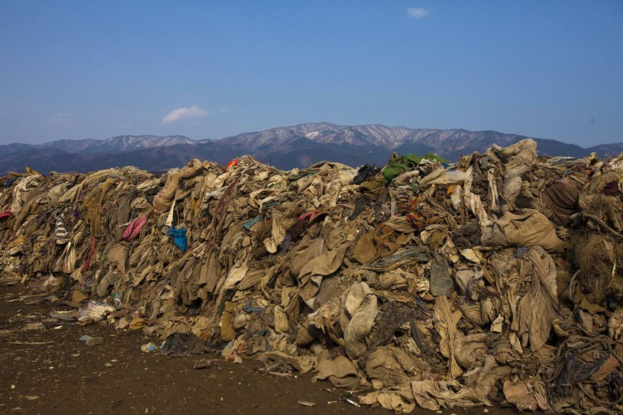 **FILE** Clothing lying in heaps at the site of a neighborhood in Rikuzentakata, Japan, destroyed by the 2011 earthquake and tsunami is seen Feb. 21, 2012. (Associated Press)