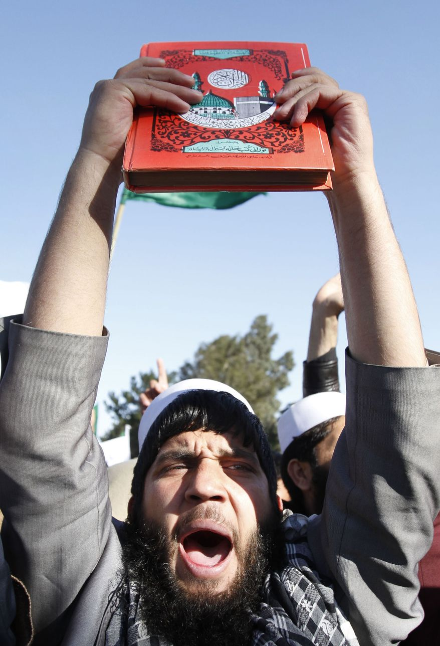 An Afghan protestor holds a copy of Islam's holy book Koran as he shouts slogans during an anti-U.S. demonstration on Feb. 22, 2012, in Jalalabad, east of Kabul, Afghanistan. (Associated Press)
