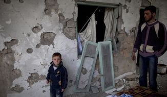 Residents stand by their house, which was destroyed in clashes between the Free Syrian Army and President Bashar Assad's forces, in Sarmin, Syria, on Tuesday, Feb. 28, 2012. (AP Photo/Rodrigo Abd)