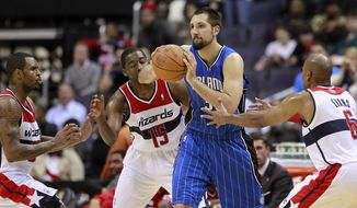 Orlando Magic forward Ryan Anderson looks for an option as he is pressured by Washington Wizards forward Trevor Booker, guard Jordan Crawford and forward Maurice Evans during the second half on Wednesday, Feb. 29, 2012, in Washington. The Magic won 102-95. (AP Photo/Haraz N. Ghanbari)