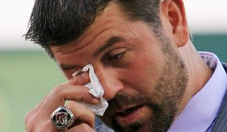 """Boston Red Sox catcher Jason Varitek wipes a tear while announcing his retirement Thursday in Fort Myers, Fla. The 39-year-old team captain says """"the hardest thing to do is walk away from your teammates"""" after 15 seasons. (Associated Press)"""