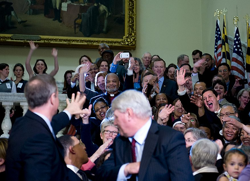 Supporters of the Civil Marriage Protection Act wave to Maryland Gov. Martin O'Malley after he and Speaker of the House Michael Busch, right, signed the act into law at the Maryland State House in Annapolis, Md., on Thursday, March 1, 2012. (Barbara L. Salisbury/The Washington Times)