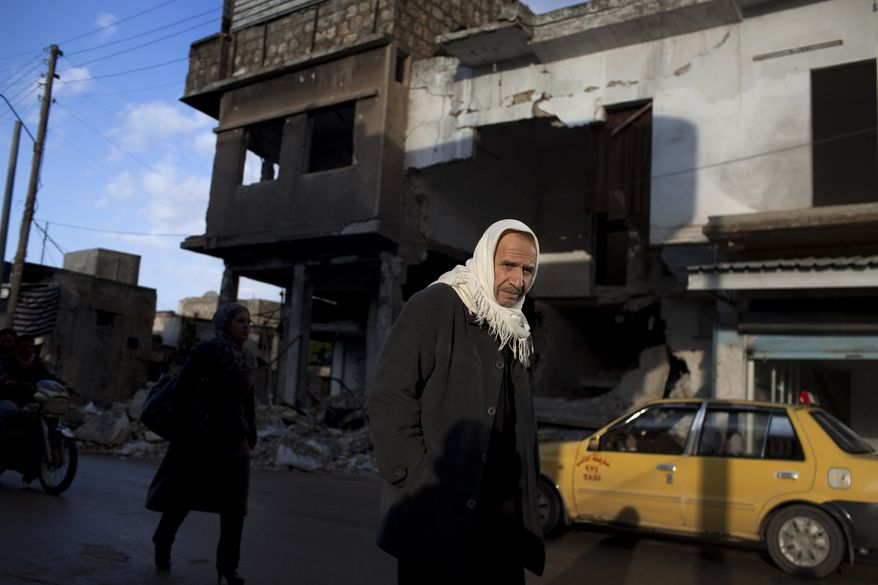 A man walks March 1, 2012, next to a damaged building due to clashes between the Free Syrian Army and government forces on the outskirts of Idlib in north Syria. (Associated Press)