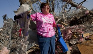 Patty Ferrell of Herod, Ill., is overcome with emotion after finding the nursing scrubs that belonged to her daughter, Jaylynn Ferrell, 22, who was killed in a tornado that struck Harrisburg, Ill., on Wednesday, Feb. 29, 2012. (AP Photo/The State Journal-Register, Justin L. Fowler)