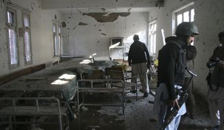 ** FILE ** Pakistani security personnel search the police station attacked by suicide attackers in Peshawar, Pakistan, on Friday, Feb 24, 2012. (AP Photo/Mohammad Sajjad)