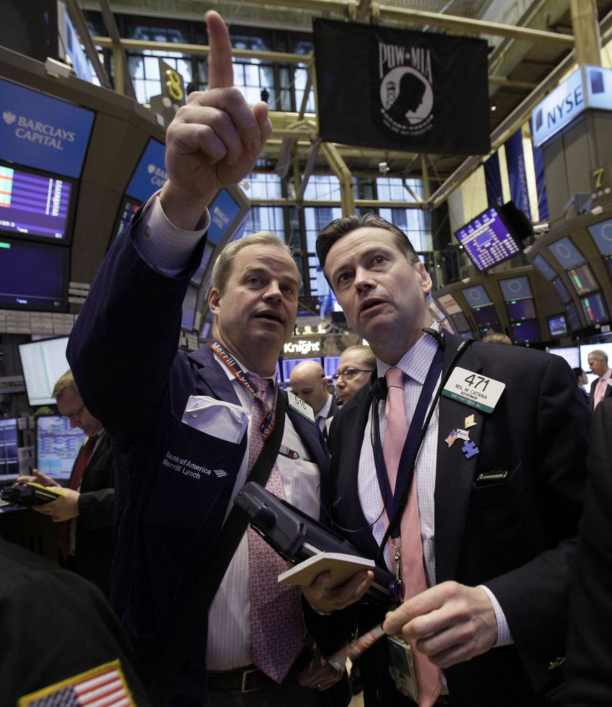 Traders David O'Day (left) and Neil Catania confer on the floor of the New York Stock Exchange on March 2, 2012. (Associated Press)