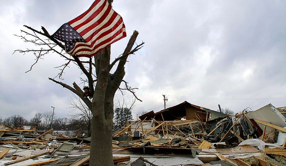 An American flag flies from what is left of the tree in front of a destroyed senior center Friday, March 2, 2012, in Harrisburg, Ill.   A pre-dawn twister flattened entire blocks of homes Wednesday as violent storms ravaged the Midwest and South.  (AP Photo/Seth Perlman)